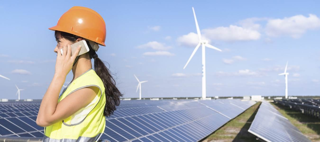 Construction worker talking on her cell phone in a field of solar panels and wind turbines.
