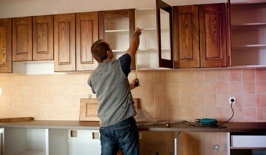Image of contractor installing kitchen cabinets