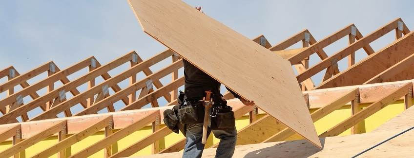 Construction worker carrying a piece of plywood on a roof.