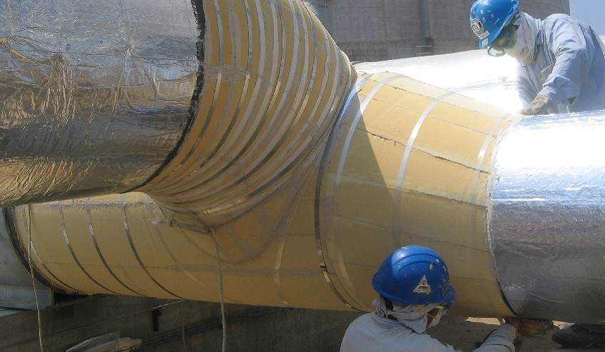 Two workers working on a large industrial application of insulation.