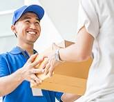 Delivery man handing over an online order in a box.